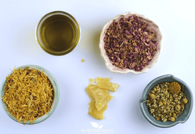 Herbal Dry Skin Salve (infused with chamomile, calendula, & roses, all pictured here)- Scratch Mommy